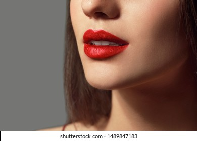 Beautiful young woman with bright lipstick on grey background, closeup
