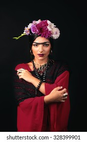 Beautiful young woman with bright make up and flowers in hair looking like Frida Kahlo. Over black background