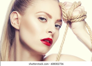 Beautiful young woman with bright make up and red lips holding rope in hand. Studio portrait. Toned