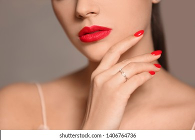 Beautiful young woman with bright manicure on color background, closeup. Nail polish trends