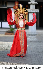 Beautiful young woman in a bright red dress and a crown of Chinese Queen posing against the ancient pavilion