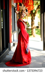 Beautiful young woman in a bright red dress and a crown of Chinese Queen posing against the ancient door.