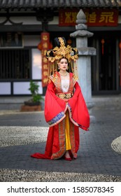 Beautiful young woman in a bright red dress and a crown of Chinese Queen posing against the ancient door. Chinese Letter means the happiness pavilion.
