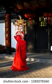 Beautiful young woman in a bright red dress and a crown of Chinese Queen posing against the ancient door. Chinese Letters meaning about the happiness pavilion.