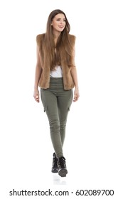 Beautiful young woman in brown fur waistcoat, khaki pants and black boots walking towards camera and looking away. Front view. Full length studio shot isolated on white.