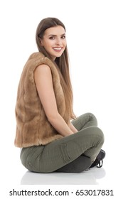 Beautiful young woman in brown fur waistcoat and khaki pants sitting on floor with legs crossed, smiling and looking at camera. Side view. Full length studio shot isolated on white.