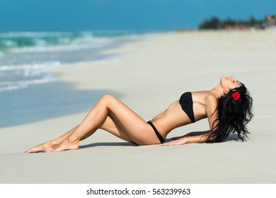 Beautiful young woman brunette with flower in hair in black swimsuit is posing on the beach on the background of azure caribbean sea at summer sunny day