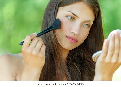 Beautiful young woman is brushed powder on face in mirror, against background of summer green park.