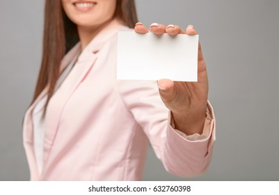 Beautiful young woman with business card on grey background, closeup