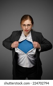 Beautiful young woman in business suit and glasses with superman concept on grey background