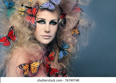 Beautiful young woman with butterfly in big curly hair.