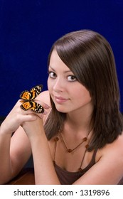 Beautiful young woman with butterfly on hand and blue background