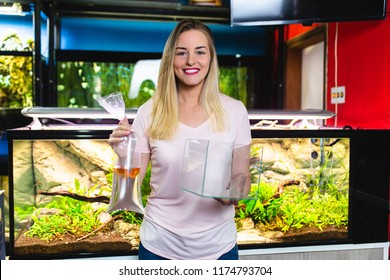 Beautiful young woman buying fishes in a fish shop.