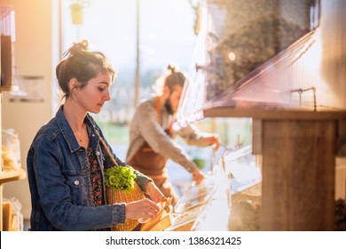 Beautiful young woman buying food in a bulk organic food store, while the seller supplies the store's departments