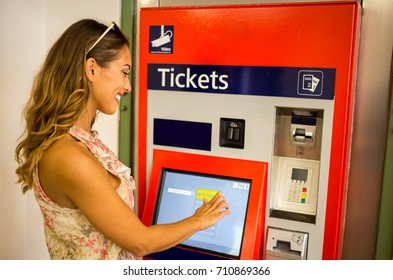 Beautiful young woman buying tickets for public transportation