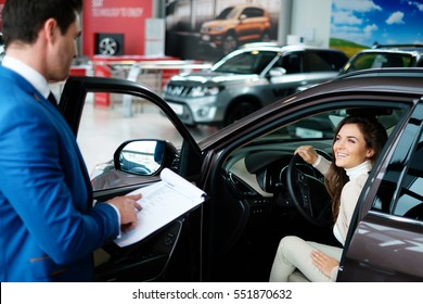 Beautiful young woman buys a car in the dealership saloon.