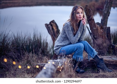 Beautiful young woman by the lake in the evening with fairy lights