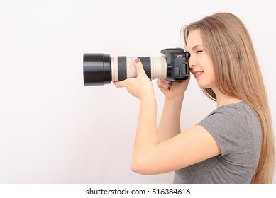 Beautiful young woman with camera. Full isolated woman with dslr. Woman holding a camera - isolated over a white background. Professional female fashion photographer taking a snapshot.