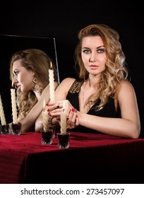 Beautiful young woman with candles near the mirror over black background