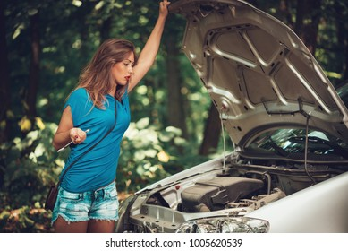 Beautiful young woman with a car that break down on the road in forest. She has standing by a car and holding wrench while looking at engine.