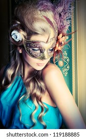 Beautiful young woman in a carnival mask over vintage background.