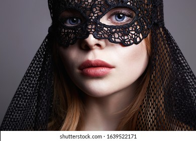 Beautiful young Woman in a Carnival Mask. Masquerade. Sexy Girl in mask. Beauty & Fashion