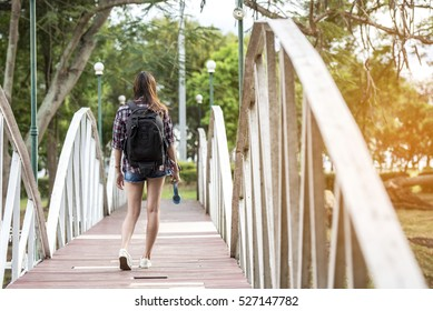 A beautiful young woman carrying a bag walking across a bridge in the park.
