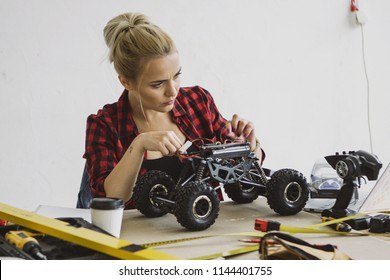 Beautiful young woman in casual checkered shirt sitting at wooden workbench with tools and fixing black radio-controlled toy car on background of white wall