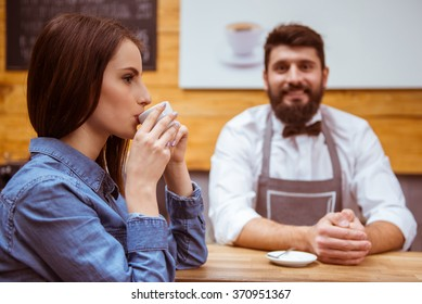 Beautiful young woman in casual clothes drinking coffee, young handsome barista with beard standing at the bar counter in the background