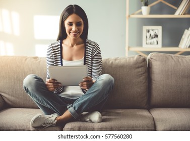 Beautiful young woman in casual clothes is using a digital tablet and smiling while sitting on couch at home