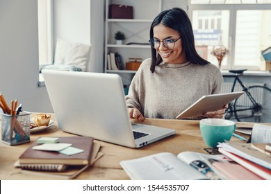 Beautiful young woman in casual clothing using laptop and smiling while working indoors