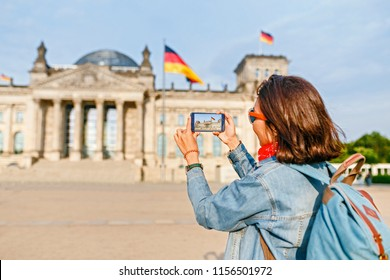 Beautiful young woman in casual wear taking photos by her mobile phone at the Bundestag, Berlin