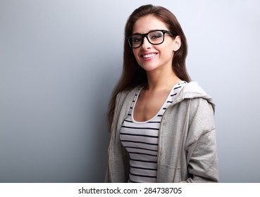 Beautiful young woman in casual wear with toothy smile on blue background with empty copy space