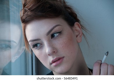 Beautiful young woman in casual wear smoking on window. Over evening  city.
