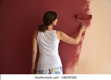 Beautiful young woman in causal clothes painting a wall with red paint and a roller