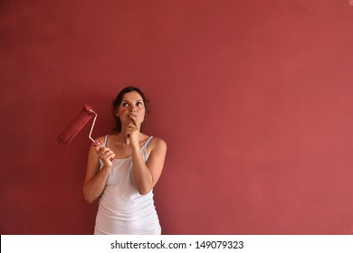 Beautiful young woman in causal clothes thinking about the result of the work she has done painting a wall with red paint and a roller
