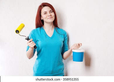 Beautiful young woman in causal clothes enjoying the result of the work she has done painting a wall.