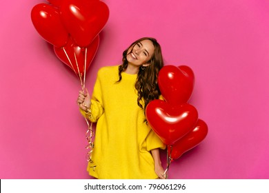 Beautiful young woman celebrating St. Valentine's day, holding red air balloons. Dressed in yellow sweater. Isolated over pink background.