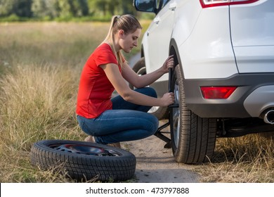 Beautiful young woman changing flat tire in field