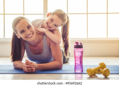 Beautiful young woman and charming little girl are looking at camera and smiling while lying on yoga mat in fitness hall