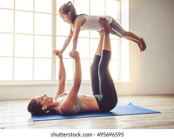 Beautiful young woman and charming little girl are smiling while doing yoga together in fitness hall