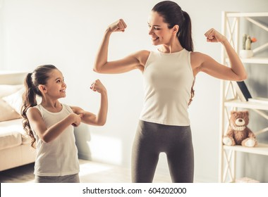Beautiful young woman and charming little daughter are showing their biceps and smiling while working out at home