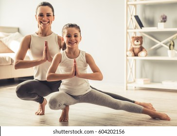 Beautiful young woman and charming little daughter are smiling while doing yoga together at home