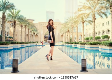 Beautiful young woman with charming smile and long hair walking on Dubai Downtown.