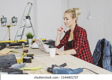 Beautiful young woman in checkered shirt sitting at wooden workbench with carpenter tools and working on laptop smiling