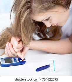 Beautiful Young Woman Checking Blood Sugar Level by Glucose Meter at Home. Medicine, Diabetes, Glycemia, Health Care Concept