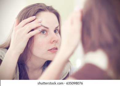 Beautiful young woman checks her eyebrows in the mirror