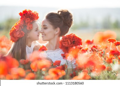 beautiful young woman with child girl in poppy field. happy family having fun in nature. outdoor portrait in poppies. mother with daughter. summer time