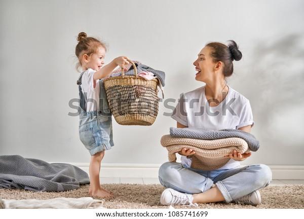 Smuk ung kvinde og barn pige lille hjælper har det sjovt og smilende mens du laver vasketøj derhjemme.
