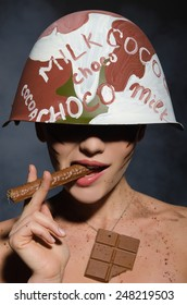 Beautiful young woman with chocolate cigar in hand and helmet